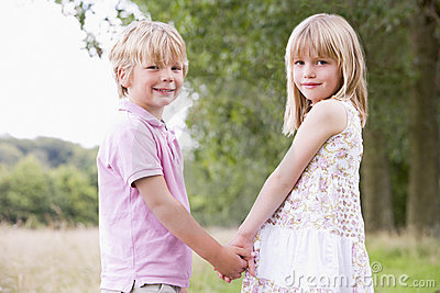 Two young children standing outdoors holding hands