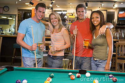 Two young couples standing beside a pool table