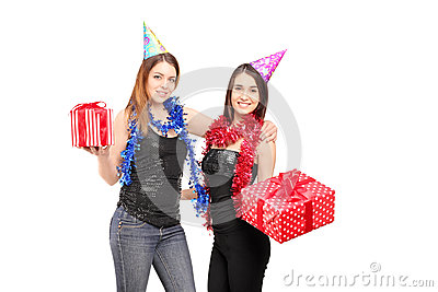 Two young female friends standing close together holdinggifts at