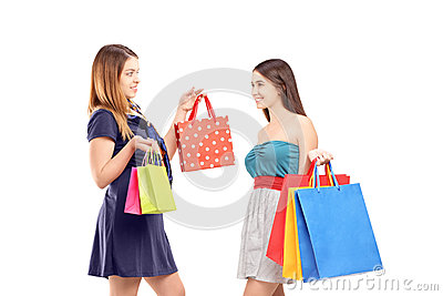 Two young females after shopping posing with shopping bags