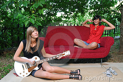 Two young friends playing the guitar