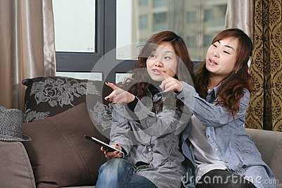 Two young girl watch TV