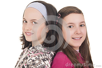 Two young girls back to back smiling