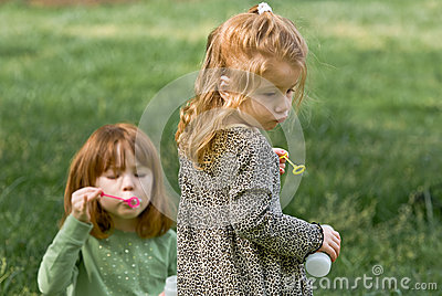 Two young girls blowing bubbles
