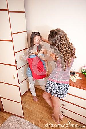 Two young girls choosing dress