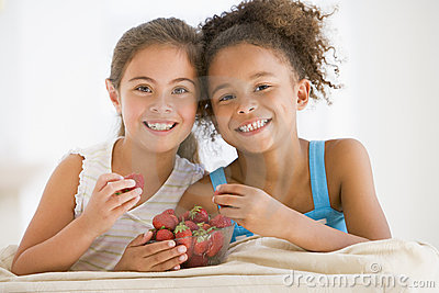 Two young girls eating strawberries