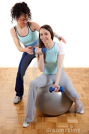 Two young girls, exercising together with weights