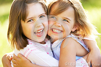 Two Young Girls Giving One Another Hug