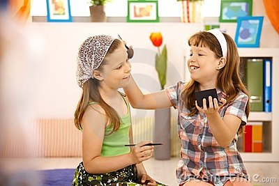 Two young girls having fun with makeup