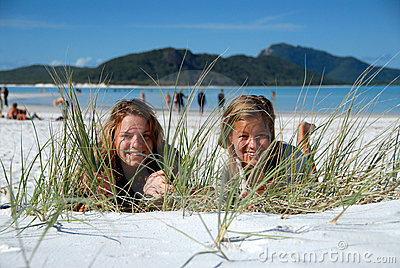 Two young girls hiding behind grass on beach