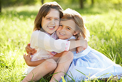Two Young Girls Hugging In Summer Field
