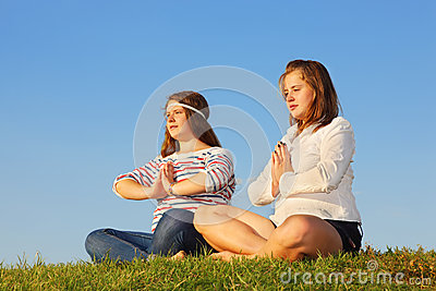 Two young girls meditate and reflect at grass