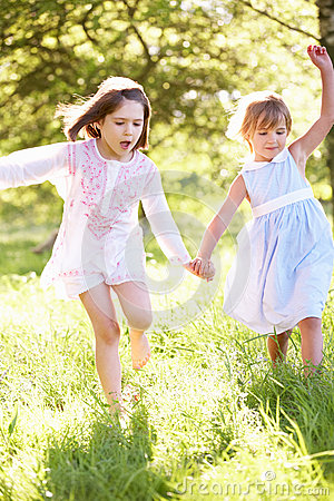 Two Young Girls Playing In Field