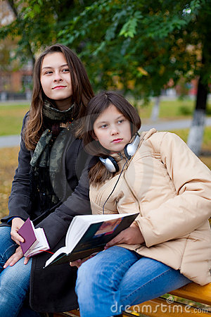 Two young girls reading in the park