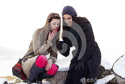 Two young girls reading text message