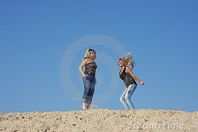 Two young  girls on a sand-pit