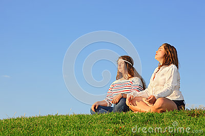 Two young girls sit and meditate at green grass
