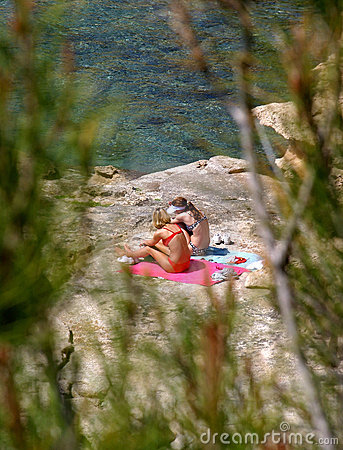 Two young girls sunbathing on rocks by the sea
