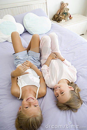 Two Young Girls In Their Pajamas Lying On A Bed