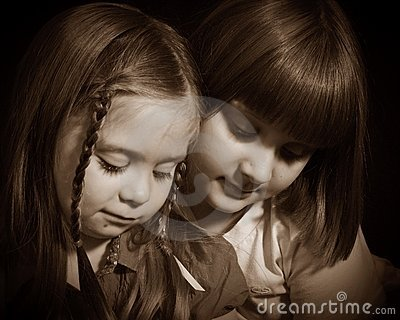 Two young girls thoughtfully looking down