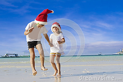 Two young happy children in santa hats on tropical beach