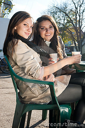 Two Young Happy Women drinking coffee and tea