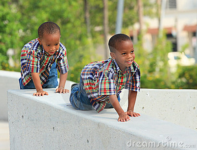 Two Young Kids Crawling On Ledge