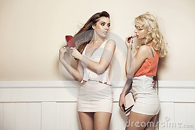 Two young beauties making preparations to a party