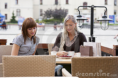 Two young lady drinking coffee