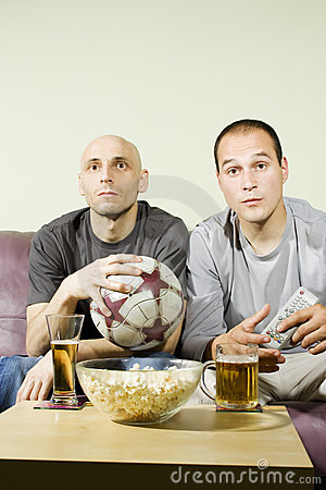 Two young men watching a football match on tv