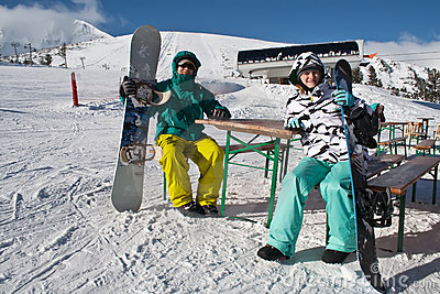 Two young people with snowboards
