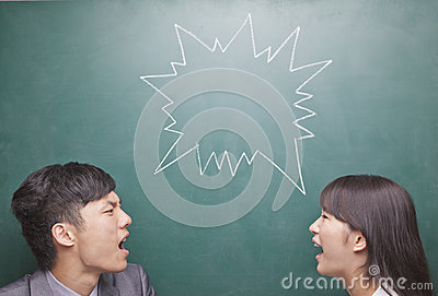 Two young people yelling at each other in front of blackboard, symbol on chalkboard