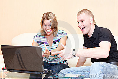 Two young persons playing in games on laptop.