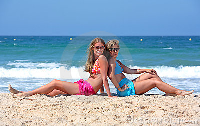 Two young sexy and healthy girls sitting on a sunny beach