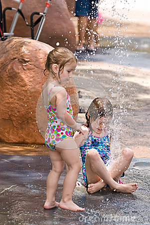 Two young sisters playing in water together