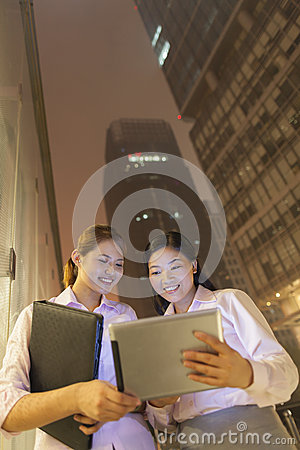 Two Young smiling businesswomen looking at digital table outdoors at night