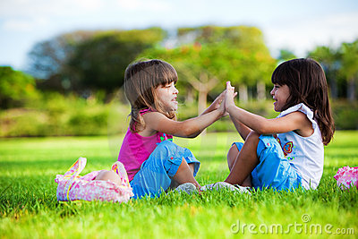Two young smiling girls sitting in the grass