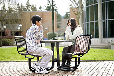 Two young teenagers sitting talking