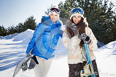 Two young woman with snowboards