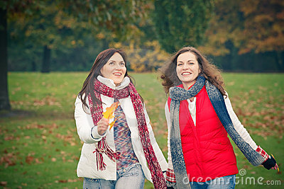 Two young woman walking in autumn park