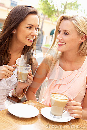 Two Young Women Enjoying Cup Of Coffee