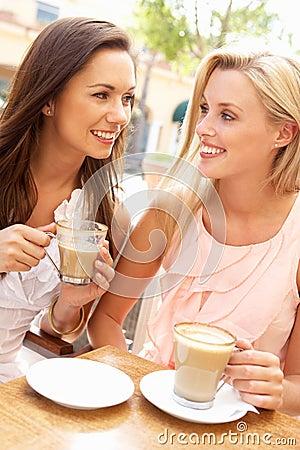 Two Young Women Enjoying Cup Of Coffee