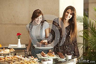 Two young women enjoying a dessert buffet