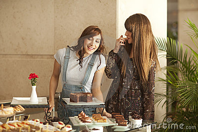 Two young women enjoying a dessert buffet