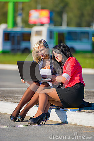 Two young women friends outdoors with a laptop