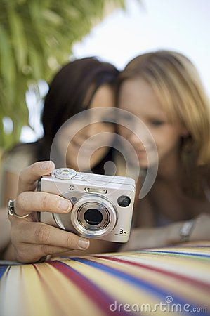 Two young women looking at pictures on digital camera in backyard focus on camera ground view