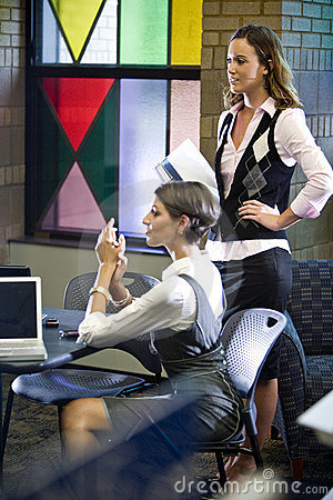 Two young women meeting with laptops at table