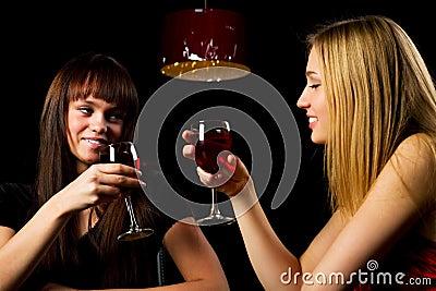 Two young fashion women in a night bar