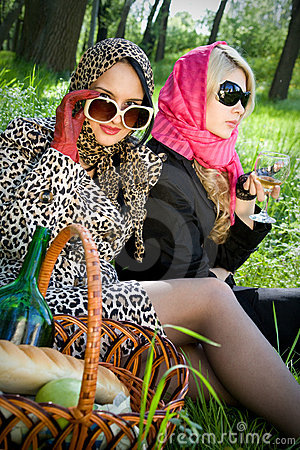 Two young women on a picnic in summer park
