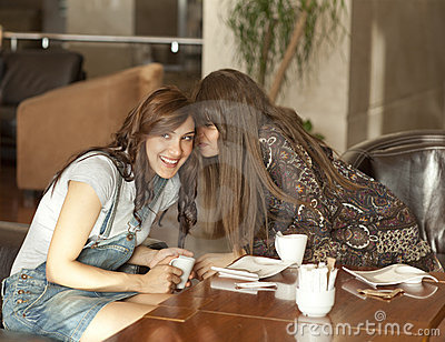 Two young women sharing a secret